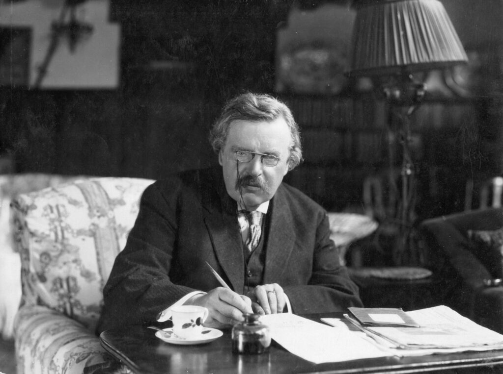 best g. k. chesterton quotes, photo of chesterton at desk