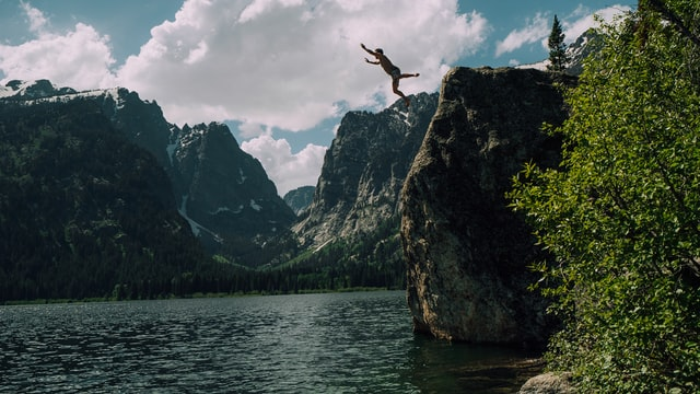 man jumping off cliff into lake