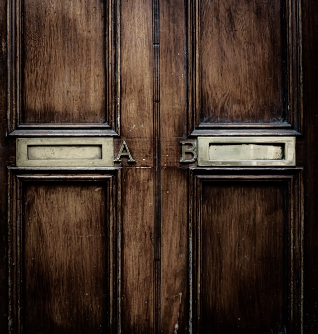 """door with two mailslots labeled """"a"""" and """"b"""""""