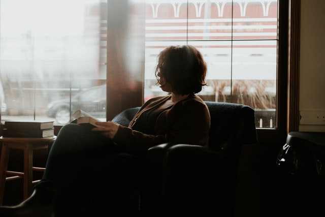 woman pausing from reading to look out window